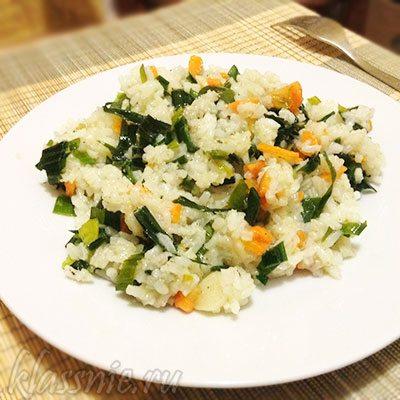 Жареный рис с луком и морковью на сковороде